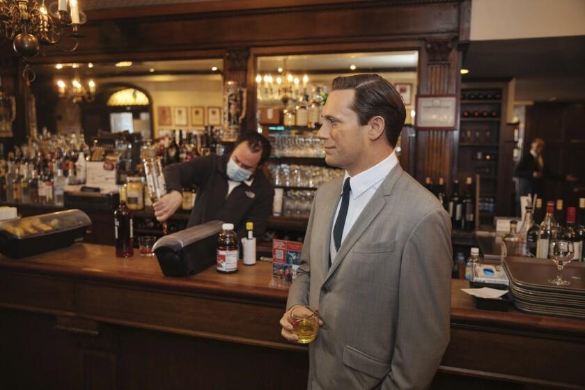 A wax statue of actor Jon Hamm stands by a bar