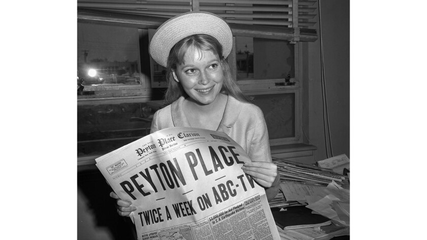 """June 16, 1964: Mia Farrow poses at the Santa Monica Courthouse with a copy of the """"Peyton Place Clarion."""""""