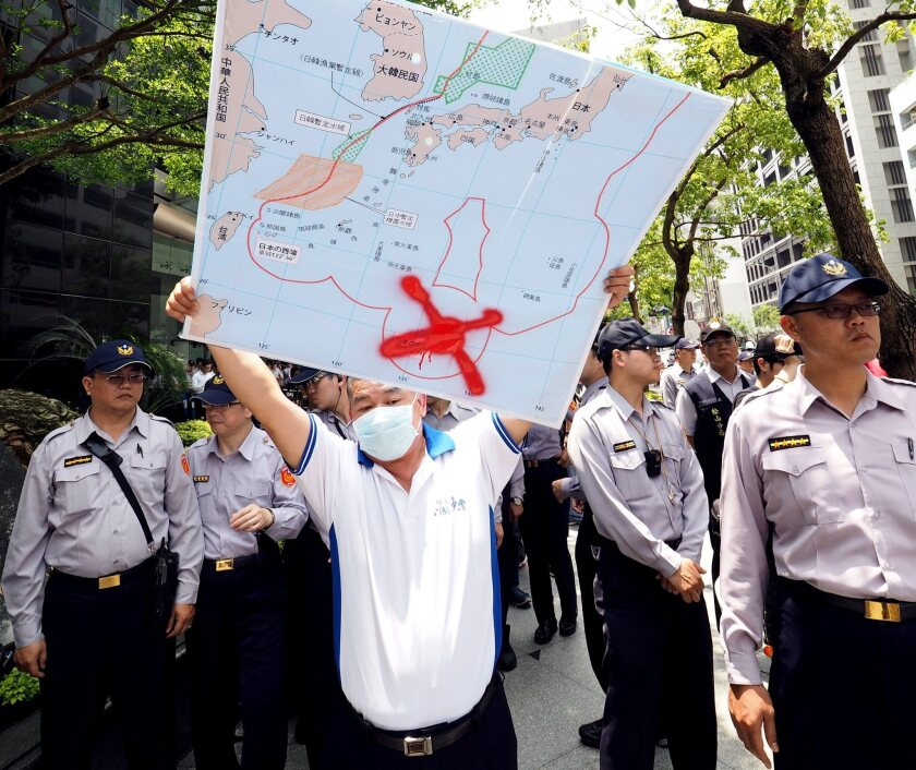 A Taiwan fisherman holds a map showing the location of the islet of Okinotori during a protest in front of Japan's representative office in Taipei, Taiwan, on April 27.