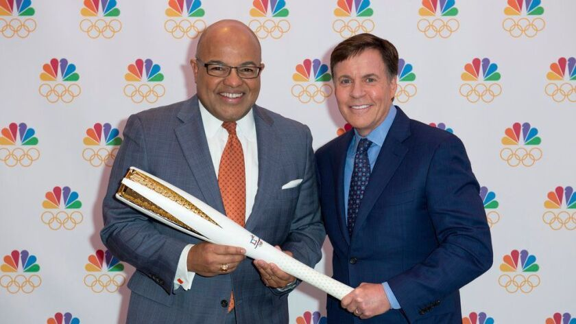 Bob Costas, right, passes the torch to Mike Tirico, who will make his debut as NBC's prime-time Olympics host, replacing Costas, at the 2018 Winter Games in Pyeongchang, South Korea.