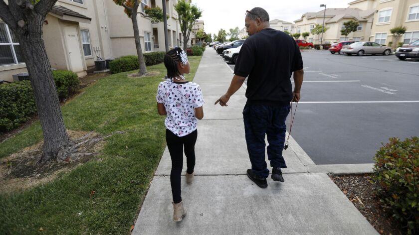 SACRAMENTO, CA May 19, 2019: Maurice Caldwell, 51, right, walks with his daughter Amaya Haynes, 9