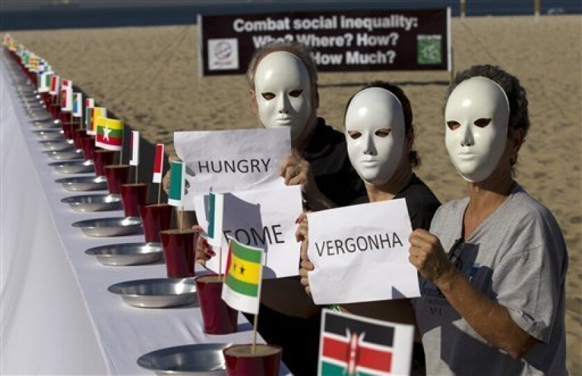"People protest beside a table set with empty plates and national flags as they hold signs that read from right to left in Portuguese; ""Shame, hunger"" at the Copacabana beach during the United Nations Conference on Sustainable Development, or  Rio+20, in Rio de Janeiro, Brazil, Tuesday, June 19, 201"