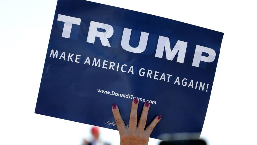 A supporter holds a pro-Trump sign in Fountain Hills, Ariz. on March 19, 2016.