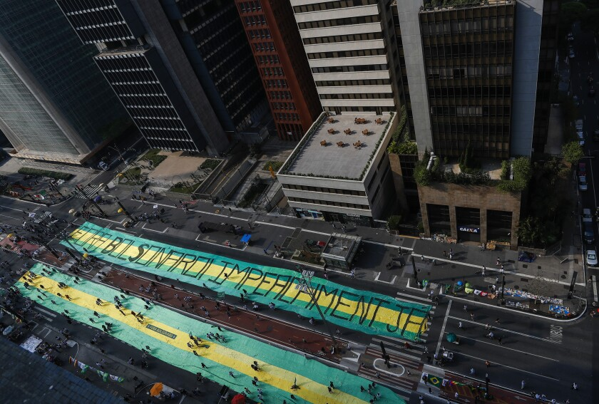 """Opposition groups extend a giant banner that reads in Portuguese """"Bolsonaro Get Out, Impeachment now,"""" during a protest against Brazilian President Jair Bolsonaro, at Avenida Paulista, Sao Paulo, Brazil, Sunday, Sep. 12, 2021. Opposition groups marched against President Jair Bolsonaro, demanding his resignation for mishandling the pandemic, corruption over vaccine contracts and a poor economy. (AP Photo/Marcelo Chello)"""