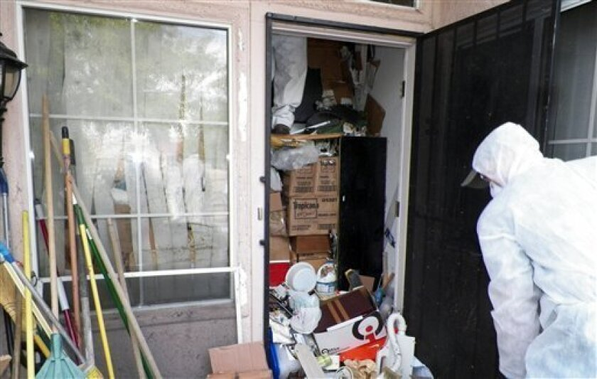 This photo provided by the City of Las Vegas via the Las Vegas Review-Journal shows a worker during a cleanup of the interior of hoarder Kenneth Epstein's home in Las Vegas. Officials began hauling away items from Kenneth Epstein's home on Friday, Oct. 5, 2012 after they found materials stacked from floor to ceiling inside and declared it uninhabitable, the Las Vegas Review-Journal reported. In all, a private removal company was working with officials to remove about 15 truckloads of materials. (AP Photo/City of Las Vegas via Las Vegas Review-Journal)