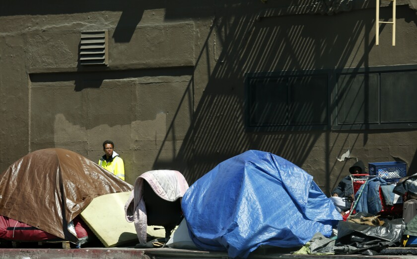 A man stands behind a cluster of tents in downtown Los Angeles.