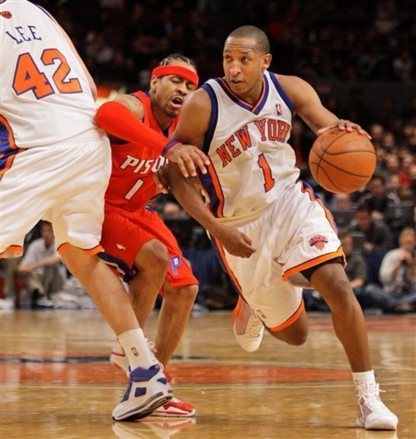New York Knicks guard Chris Duhon (1) squeezes out Detroit Pistons guard Allen Iverson (1) as he drives toward the basket with Knicks forward David Lee (42) defending in the second quarter of their NBA basketball game at Madison Square Garden in New York, Sunday, Dec. 7, 2008. (AP Photo/Kathy Willens)
