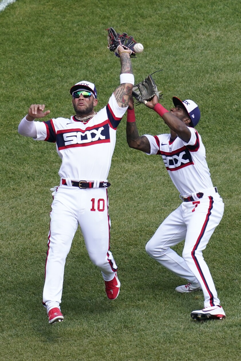 Chicago White Sox third baseman Yoan Moncada, left, makes a fielding error as teammate Tim Anderson, right, watches the ball during the fourth inning of a baseball game in Chicago, Sunday, May 2, 2021. (AP Photo/Nam Y. Huh)