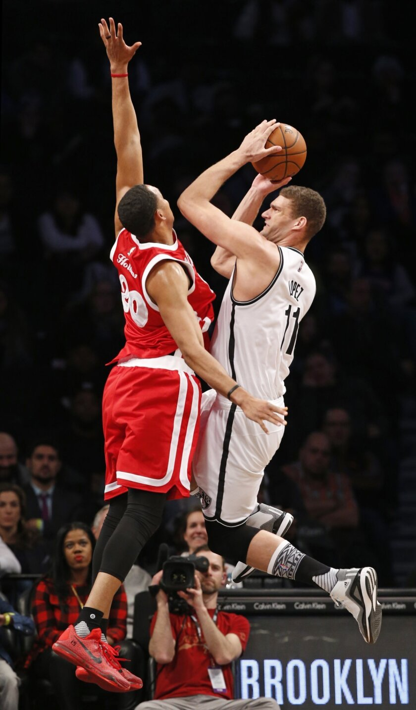 Memphis Grizzlies center Ryan Hollins (20) defends Brooklyn Nets center Brook Lopez (11) during the first half of an NBA basketball game Wednesday, Feb. 10, 2016, in New York. (AP Photo/Kathy Willens)