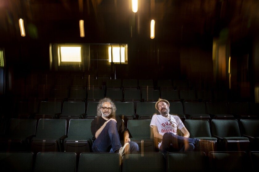 Two men sitting in green upholstered theater seats