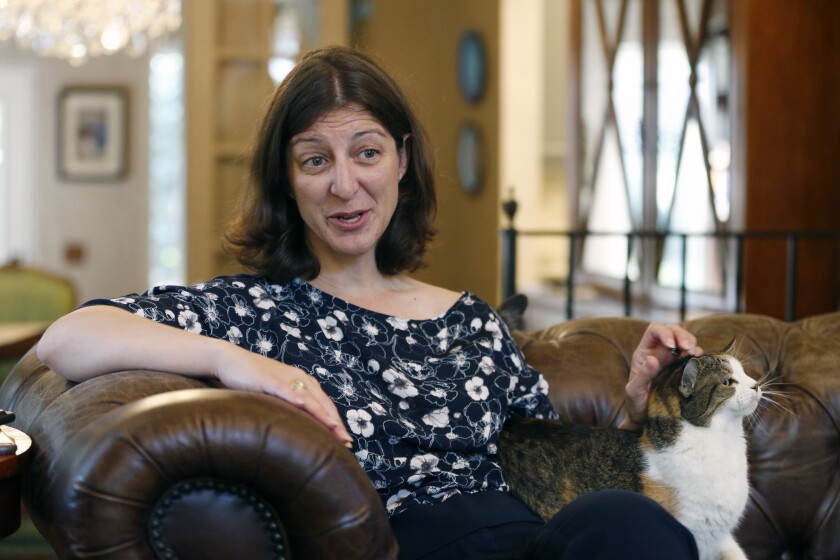 Rep. Elaine Luria, D-Va., pets her cat, Bijous, during an interview in her home in Norfolk, Va., Thursday, Oct. 3, 2019. Luria recently joined a group of other Congresswomen to call for the impeachment of President Trump. (AP Photo/Steve Helber)