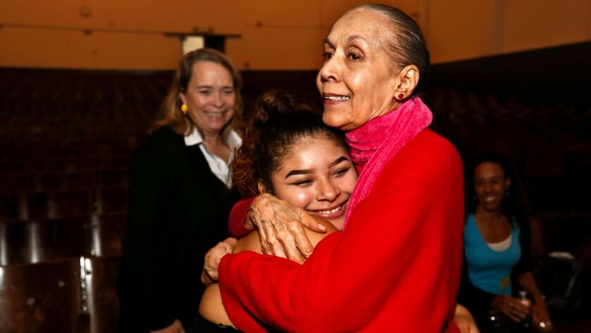 Carmen de Lavallade hugs 11th-grader Reyna Soriano, who performed a solo to welcome the dancer to Thomas Jefferson High.