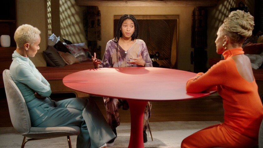 One woman talking to two older women sitting at a red table