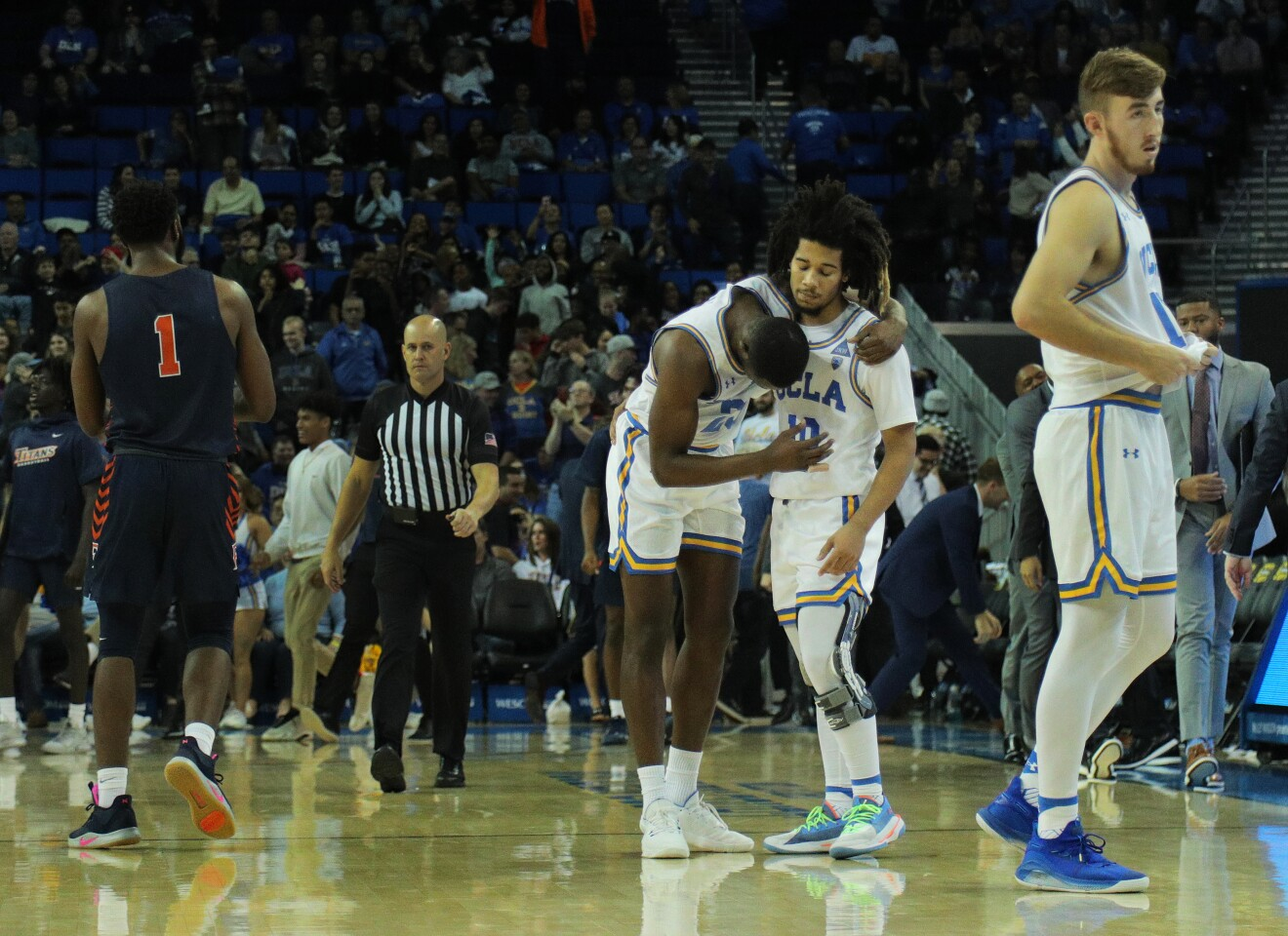 WESTWOOD, CA - DECEMBER 28, 2019: UCLA Bruins guard Tyger Campbell (10) consoles UCLA Bruins guard Prince Ali (23) after Ali turned the ball her in the final seconds of the Bruins 77-74 loss to Cal State Fullerton at Pauley Pavilion on December 28, 2019 in Westwood, California.(Gina Ferazzi/Los AngelesTimes)
