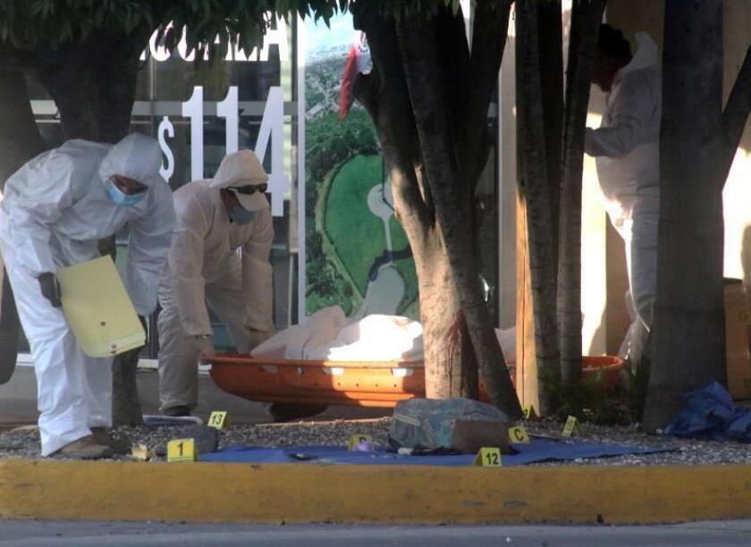 Peritos forenses recogen evidencias en el sitio donde un grupo armado mató a cinco personas que habían buscado refugio en el lugar, este lunes en una terminal de autobuses de la ciudad de Cuernavaca, en el céntrico estado de Morelos (México). EFE/STR