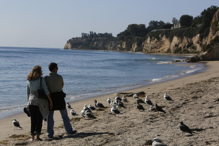 A couple strolls along the beach at Malibu's Paradise Cove. The Coastal Commission is looking into complaints that public access is restricted.