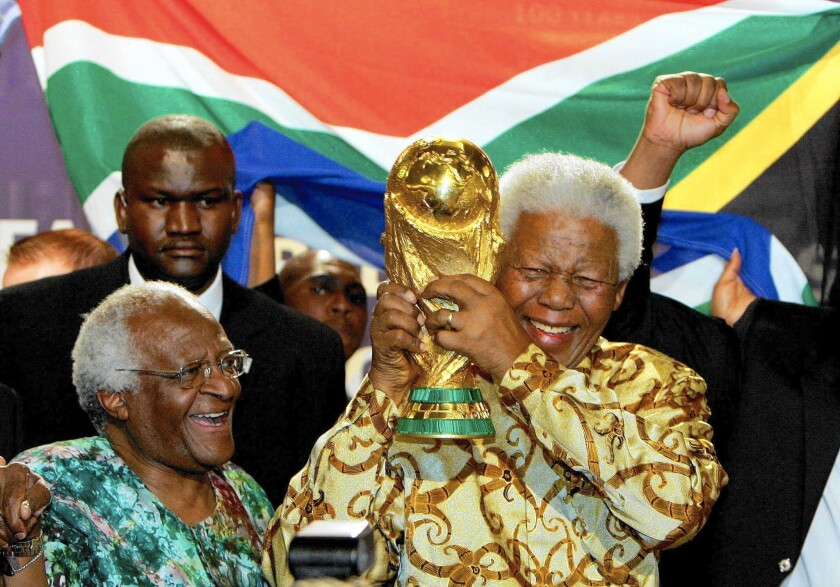 Nelson Mandela, with Capetown Archbishop Desmond Tutu, raises the Jules Rimet World Cup in Zurich in 2004, after FIFA announced that South Africa would host the 2010 World Cup.