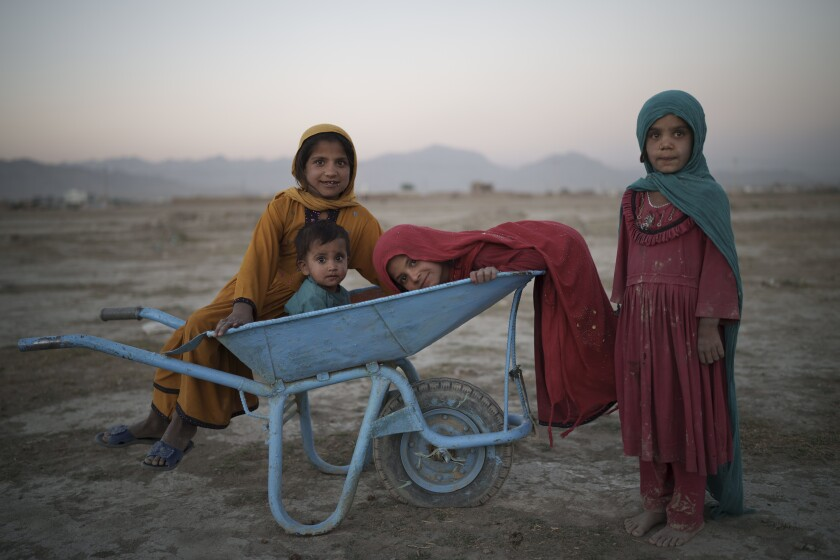 En esta imagen de archivo, tomada el 13 de septiembre de 2021, cuatro niños posan para una fotografía mientras juegan en un campamento para desplazados en Kabul, Afganistán. (AP Foto/Felipe Dana, archivo)
