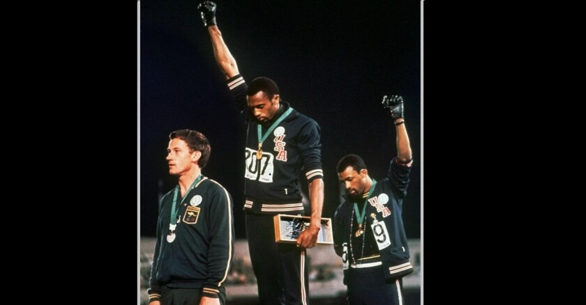 "Tommie Smith, center, and John Carlos raise their fists during ""The Star-Spangled Banner"" after Smith received the gold and Carlos the bronze for the 200-meter run at the 1968 Summer Olympics in Mexico City."