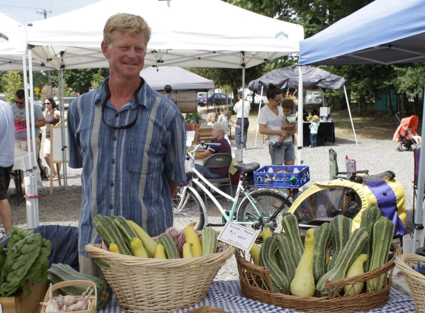 Urban farmer Richard Dickinson sells vegetables at the Lent's International Farmers Market in East Portland, Ore. on July 12, 2015.