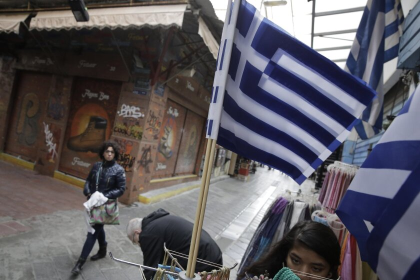 Greek flags fly as a tourist walks by a souvenir shop in Athens.