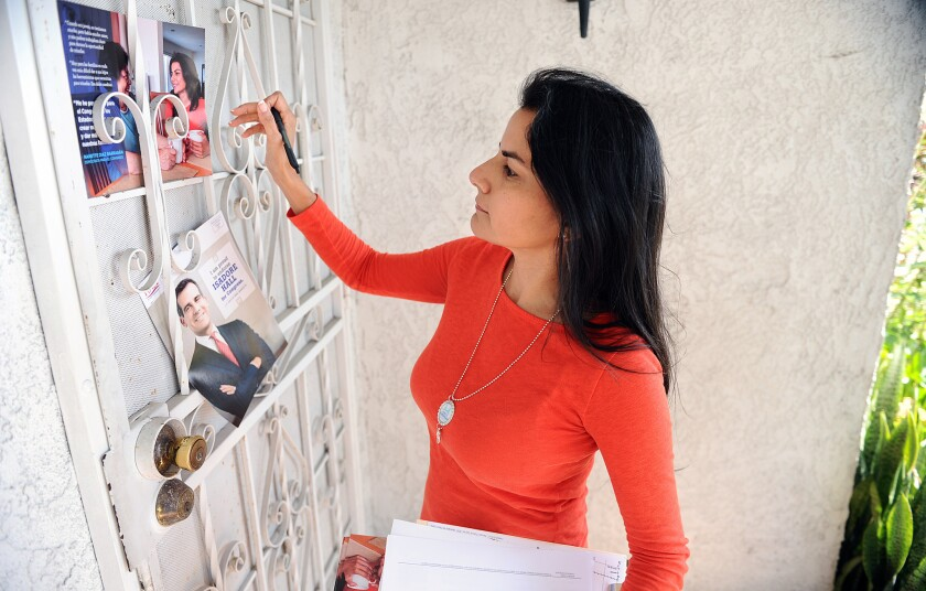 Nanette Barragán leaves a flier on a house in South Gate in late May. She was elected to California's 44th Congressional District Tuesday.