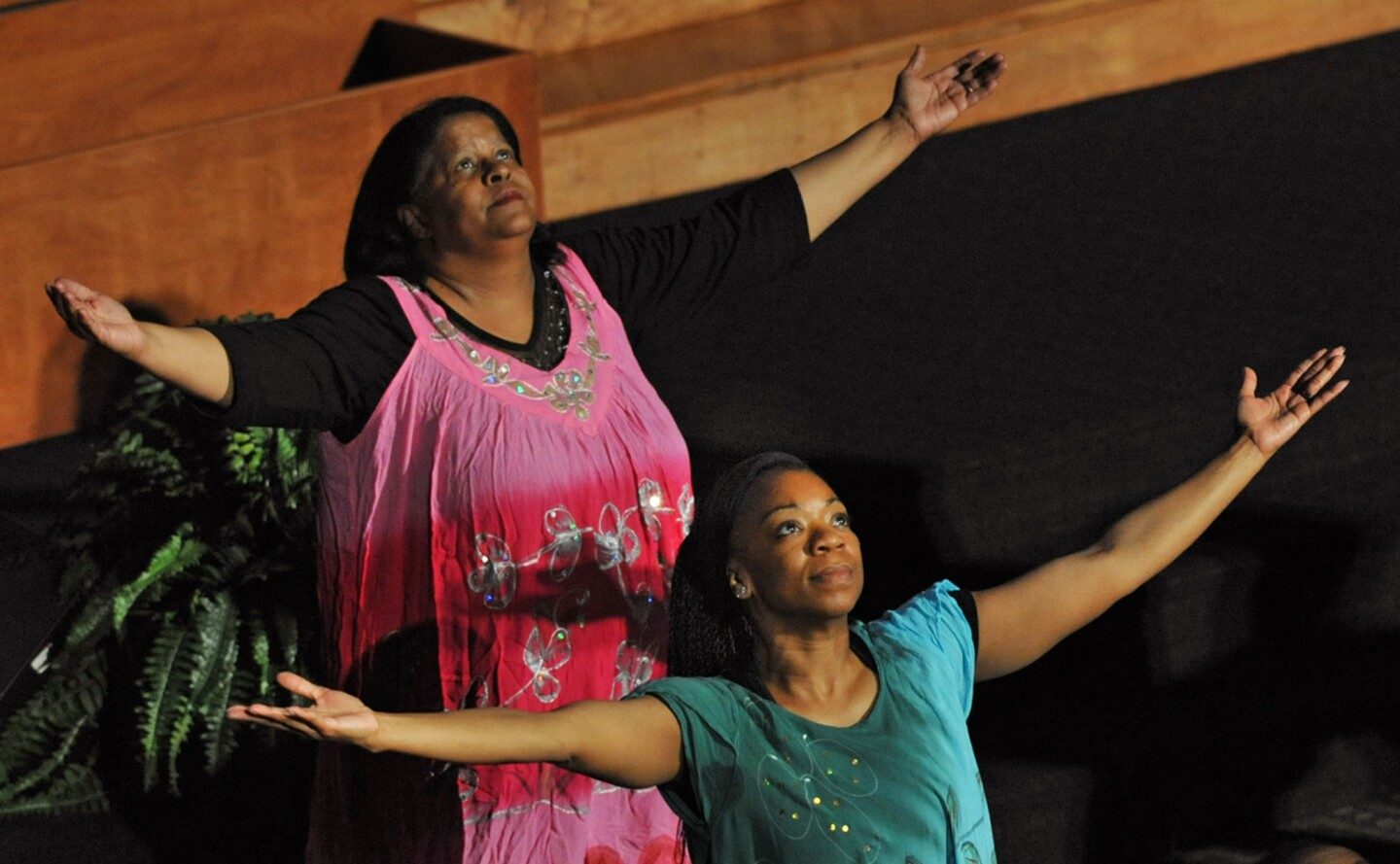 Two members of the New Psalmist Prophetic Praise Dance Ministry perform during the city-wide prayer service held Thursday night at the New Psalmist Baptist Church. Churches from all denominations came together in response to the riot and protests.