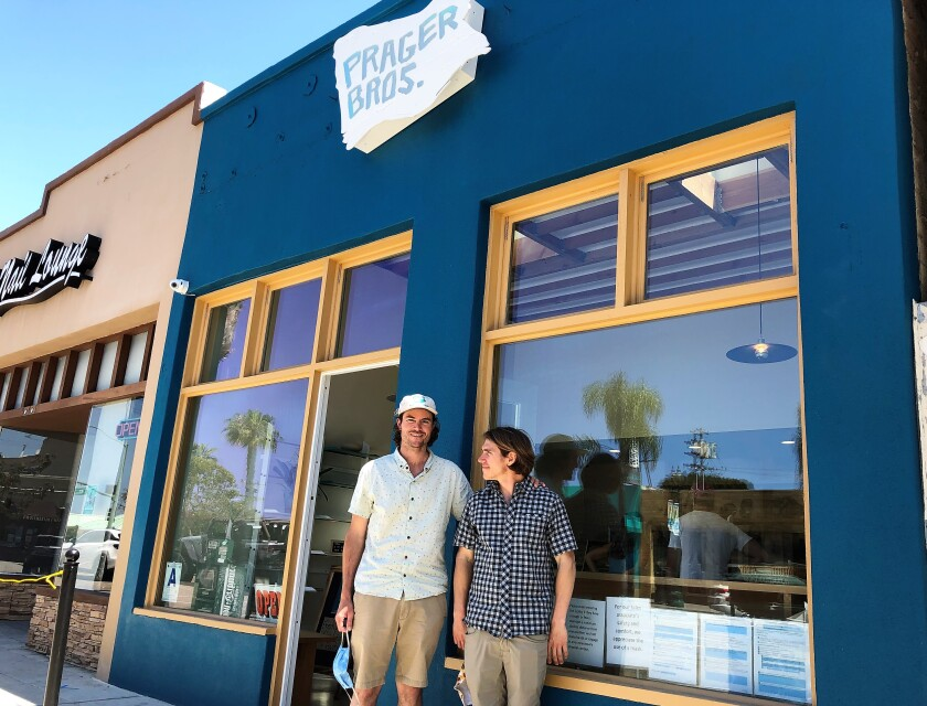 Siblings Louie Prager, left, and Clinton Prager wait outside their newly opened Prager Bros. Artisan Breads store in downtown Encinitas on April 25. Despite opening the shop during the pandemic on April 17, the brothers say the shop has been surprisingly busy.