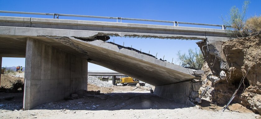Construction workers stand near the collapsed elevated section of Interstate 10, Wednesday, July 22, 2015, near Desert Center, Calif. Yuma, Ariz., usually a sleepy desert town , is seeing thousands more visitors as traffic between Phoenix and Los Angeles is rerouted due to the collapsed freeway bridge to the north. Crews continued worked to fortify the bridge that a surge of floodwater damaged, with a goal to reopen the main route between Los Angeles and Phoenix by Friday. (Tom Tingle/The Arizona Republic via AP)
