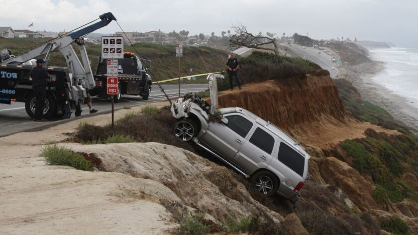 Carlsbad police supervise the removal of Junior Seau's Cadillac Escalade after he crashed it over a