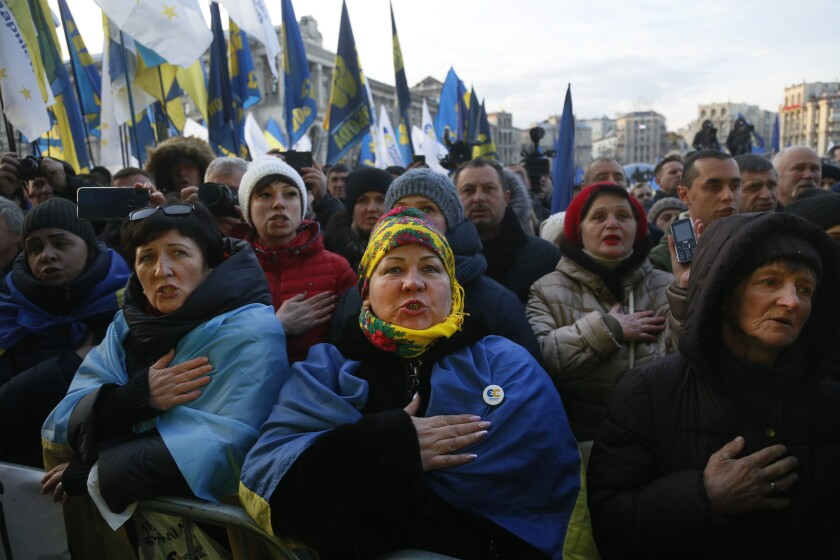 Activists sing the national anthem during a rally in central Kyiv, Ukraine, Sunday, Dec. 8, 2019. A few thousand activists demanded to withdraw the Russian troops from currently occupied Donetsk and Luhansk regions in Ukraine's east on the eve of Monday peace talks in Paris with Russian President Vladimir Putin and Ukrainian President Volodymyr Zelenskiy. ( AP Photo/Efrem Lukatsky)