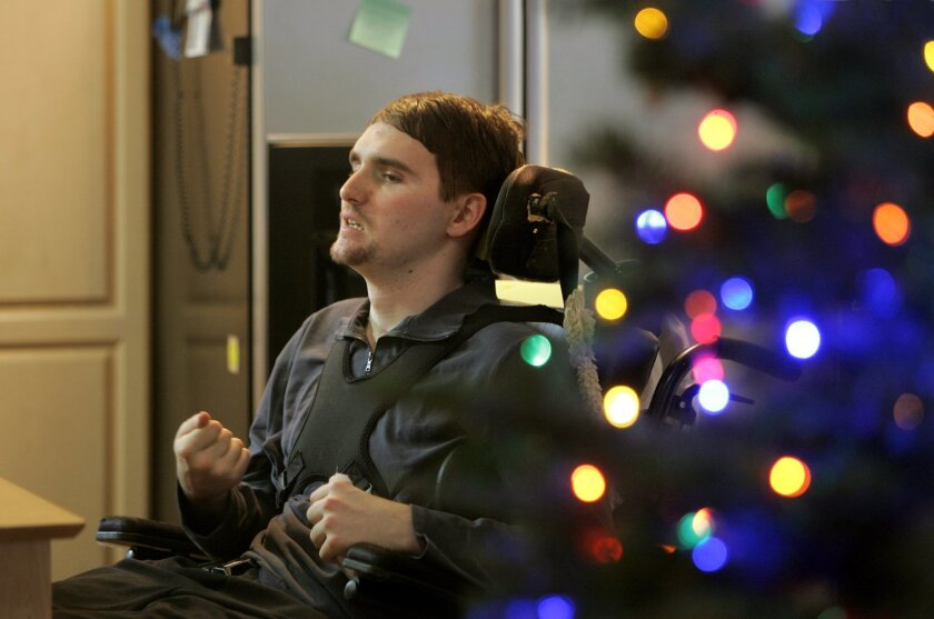 Scotty Eveland sits in his wheelchair at home during the holiday season.