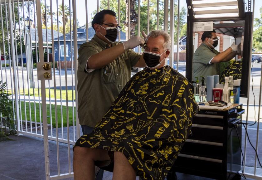 Obie Figueroa, owner of Obie's Barbershop & Shave in Riverside, cuts San Dimas resident Matt Nelson's hair Tuesday