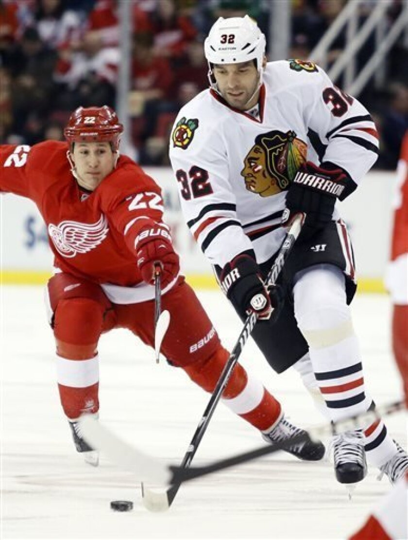 Detroit Red Wings right wing Jordin Tootoo (22) tries to reach Chicago Blackhawks defenseman Michal Rozsival (32), of the Czech Republic, as he brings the puck down the ice in the first period of an NHL hockey game Sunday  March 31, 2013, in Detroit. (AP Photo/Duane Burleson)