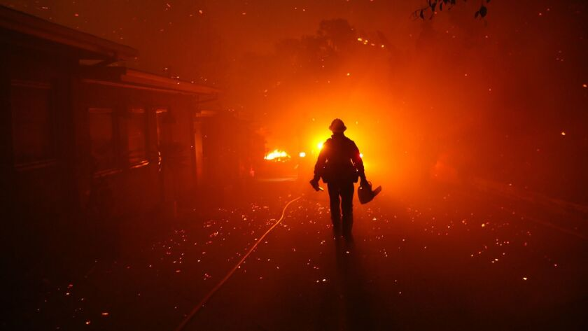 A firefighter walks toward his engine after trying to prevent the Woolsey fire from overtaking structures in Malibu.