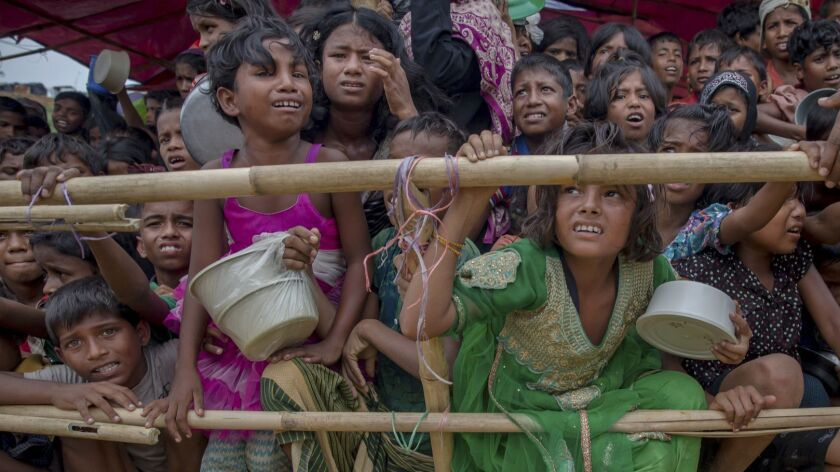FILE - In this Saturday, Oct. 21, 2017, file photo, Rohingya Muslim children wait for food handouts