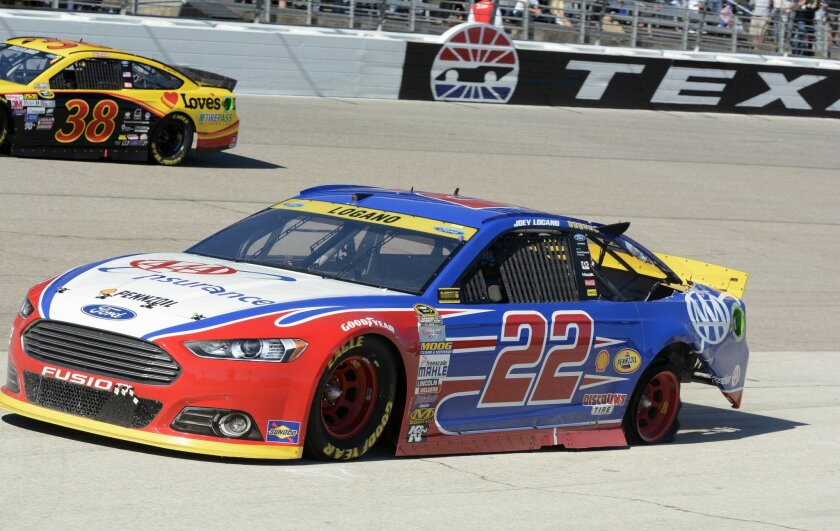 Joey Logano (22) pulls onto pit row with a shredded back tire during the NASCAR Sprint Cup Series auto race at Texas Motor Speedway in Fort Worth, Texas, Sunday, Nov. 8, 2015. (AP Photo/Larry Papke)