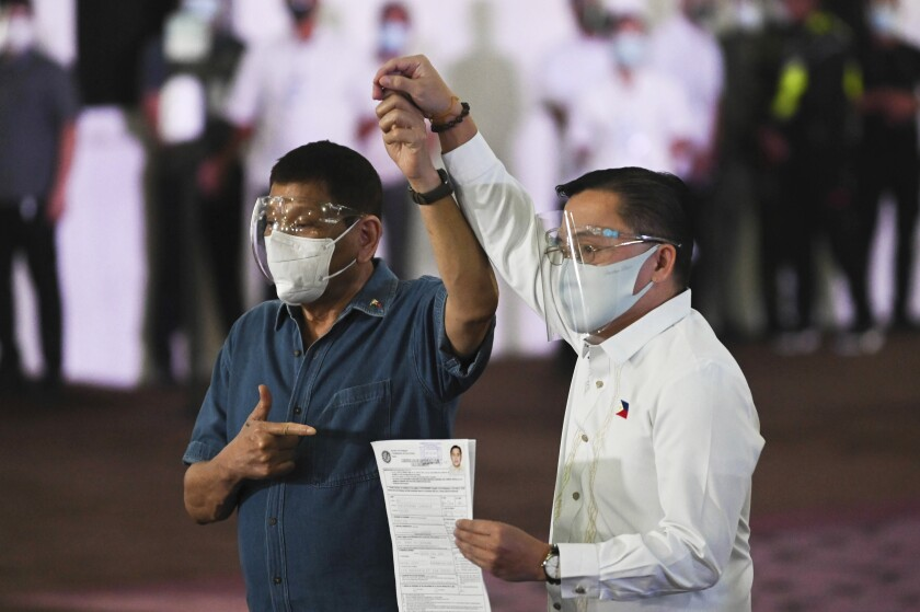 Philippine President Rodrigo Duterte, left, raises the hand of Sen. Bong Go who has filed his certificate of candidacy for vice-president during next year's elections before the Commission on Elections at the Sofitel Harbor Garden Tent in Metropolitan Manila, Philippines on Saturday, Oct. 2, 2021. Duterte says he is backing out of an announced plan to run for vice president in next year's elections and will retire from politics after his term ends. (Lisa Marie David/Pool Photo via AP)