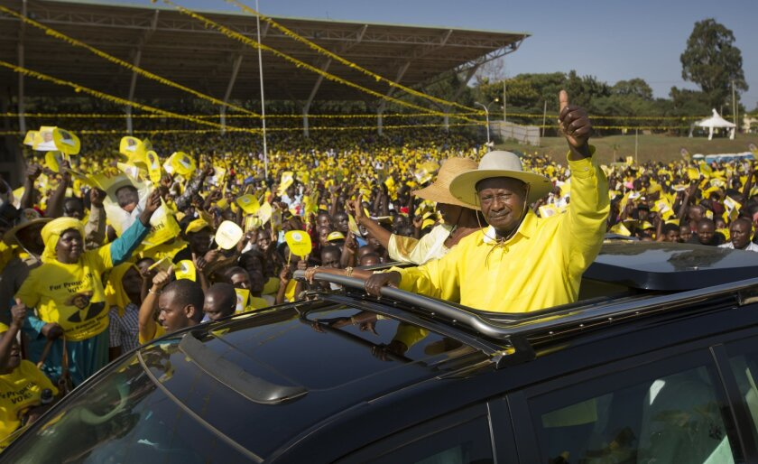 Uganda's long-time President Yoweri Museveni waves to supporters from the sunroof of his vehicle as he arrives for an election rally at Kololo Airstrip in Kampala, Uganda Tuesday, Feb. 16, 2016. Opposition leader Kizza Besigye, in a close race with Museveni, said Tuesday he does not believe the ele