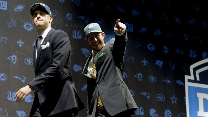 Jared Goff, left, after being selected by Los Angeles Rams as their number one overall pick and Cars
