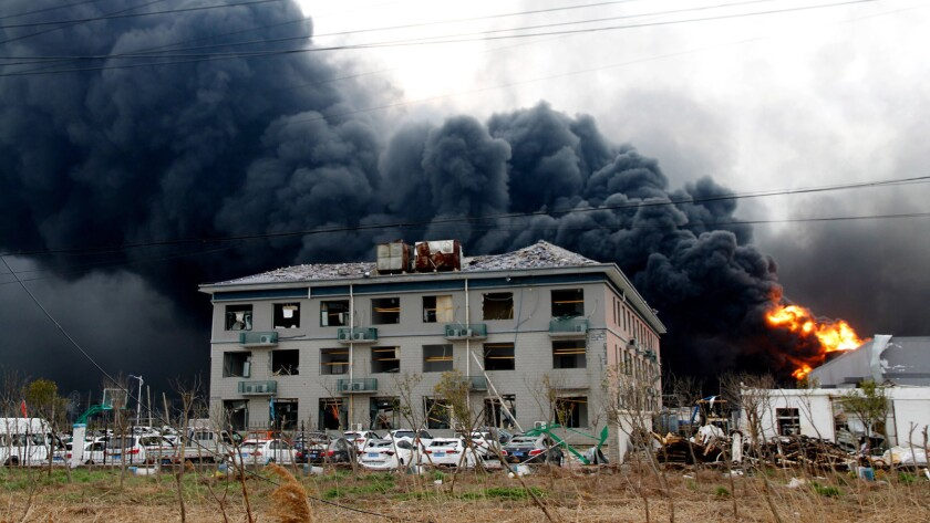 In this Thursday, March 21, 2019, photo, fires burn at the site of a factory explosion in a chemical