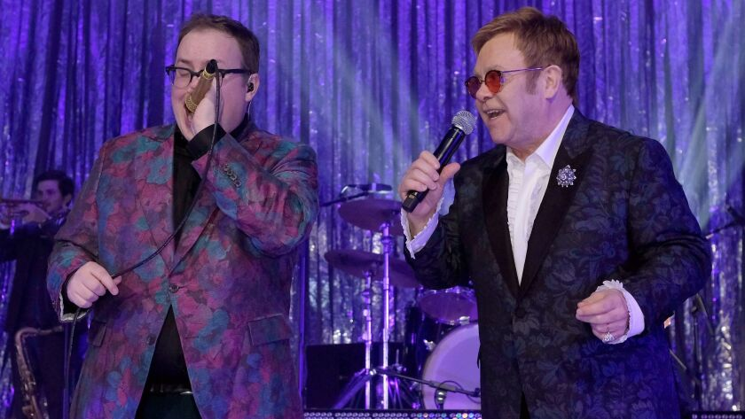 Singer Paul Janeway, left, of St. Paul & the Broken Bones and host Elton John duet during Sunday's 25th Academy Awards viewing party that raised $7 million for the Elton John AIDS Foundation.