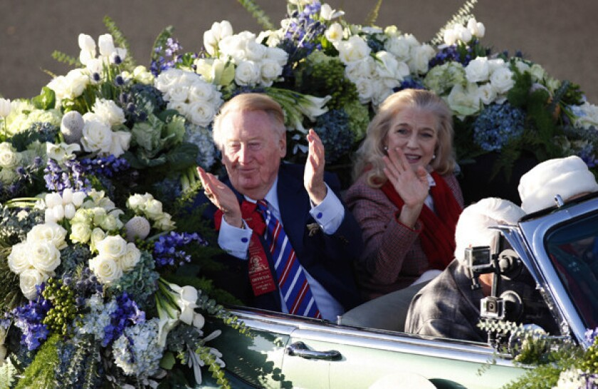 """Dodgers broadcaster Vin Scully and his wife Sandi acknowledge the crowd while riding in a car during Wednesday's Rose Parade. Scully says the honor of serving as the parade's grand marshal has been a """"marvelous treat"""" for him."""