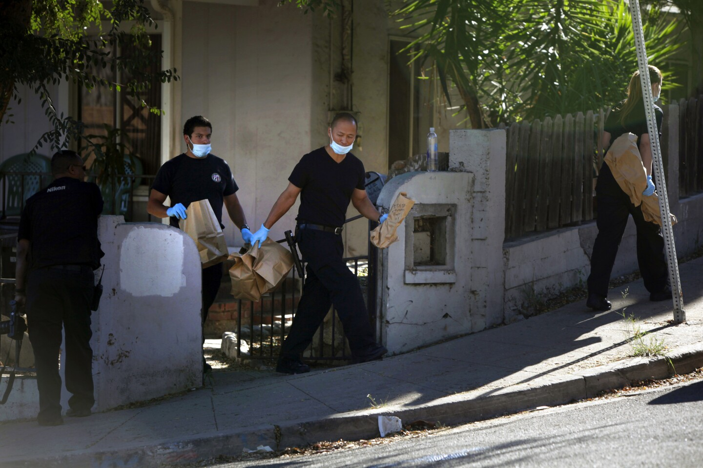 Police carry items away from a residence in the 4400 block of Topaz Street in Montecito Heights. Police served a series of search warrants in November in the neighborhood and detained some people for questioning as they continued investigating the deaths of two teenagers whose bodies were found in a park.
