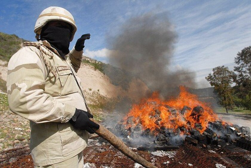 A Mexican army soldier shields his face from the heat after prodding packages of drugs that are being incinerated at a military base in Tijuana.