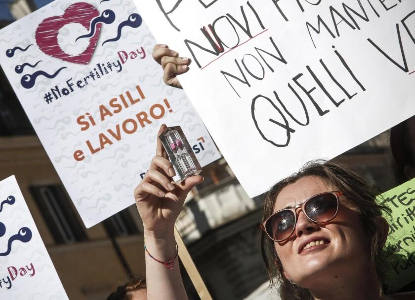 """Una mujer sostiene un reloj de arena durante una protesta enfrente del ministerio de Salud de Italia, en el lanzamiento de la campaña """"Dia de la Fertilidad"""", el jueves 22 de septiembre del 2016, en Roma, Italia. (Giuseppe Lami/ANSA via AP)"""