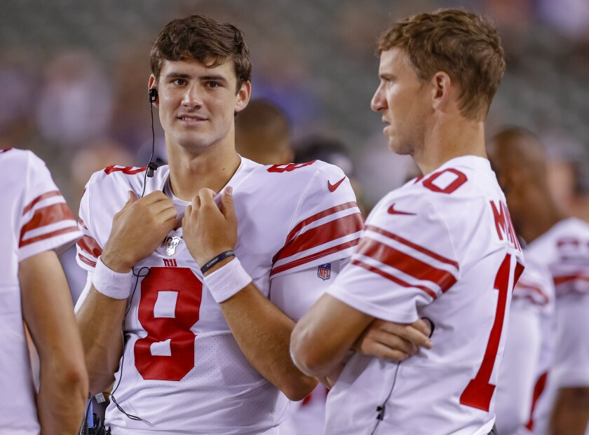 New Giants starting quarterback Daniel Jones, left, talks with the former starter, Eli Manning.