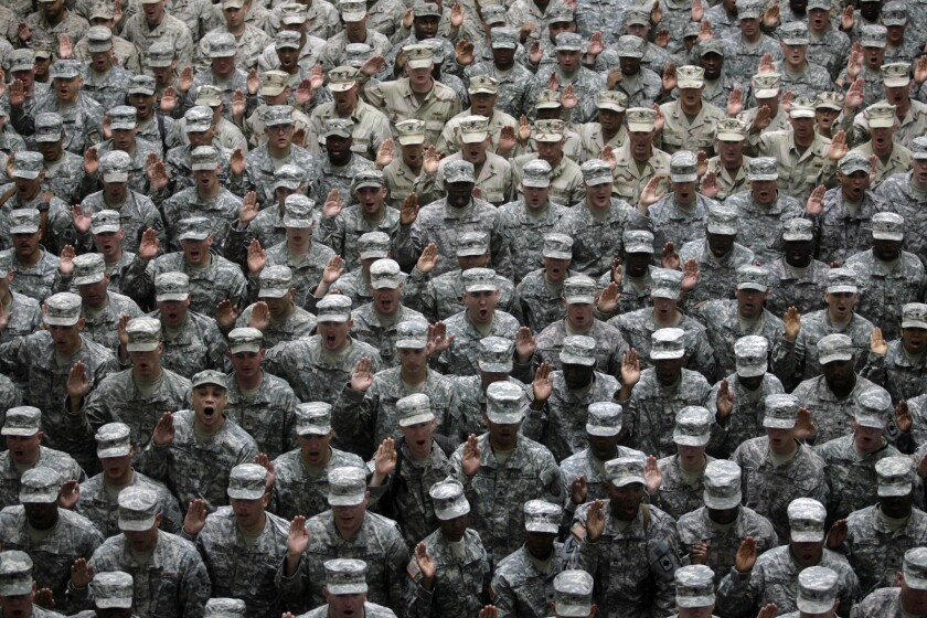 U.S. military service members take an oath at a mass reenlistment ceremony in Baghdad, Iraq, on July 4, 2008.