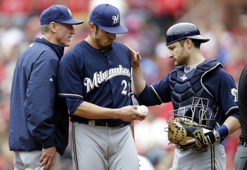 Milwaukee Brewers starting pitcher Matt Garza, center, gets a pat on the back from catcher Jonathan Lucroy while leaving a baseball game due to an injury as manager Ron Roenicke, left, stands by during the fourth inning of a baseball game against the St. Louis Cardinals Wednesday, April 30, 2014, i