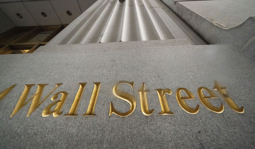 A sign for Wall Street is carved in the side of a building, Thursday, Nov. 5, 2020, in New York. U.S. futures and world shares have surged as investors await the outcome of the U.S. presidential election and embrace the upside of more gridlock in Washington. (AP Photo/Mark Lennihan)